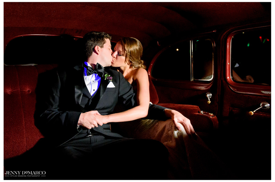 The newly weds share a kiss in their getaway car.