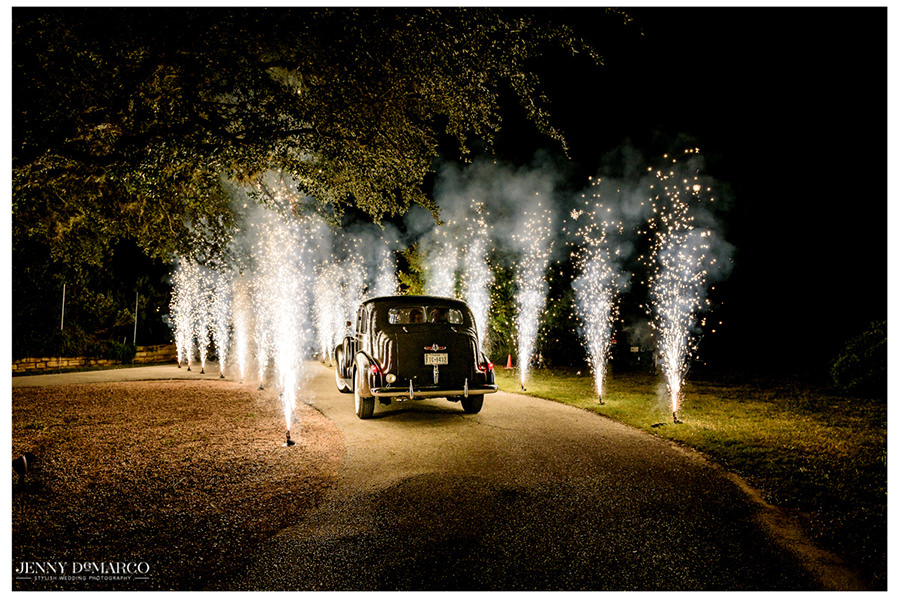 The car leaves the reception through a firework lined road.