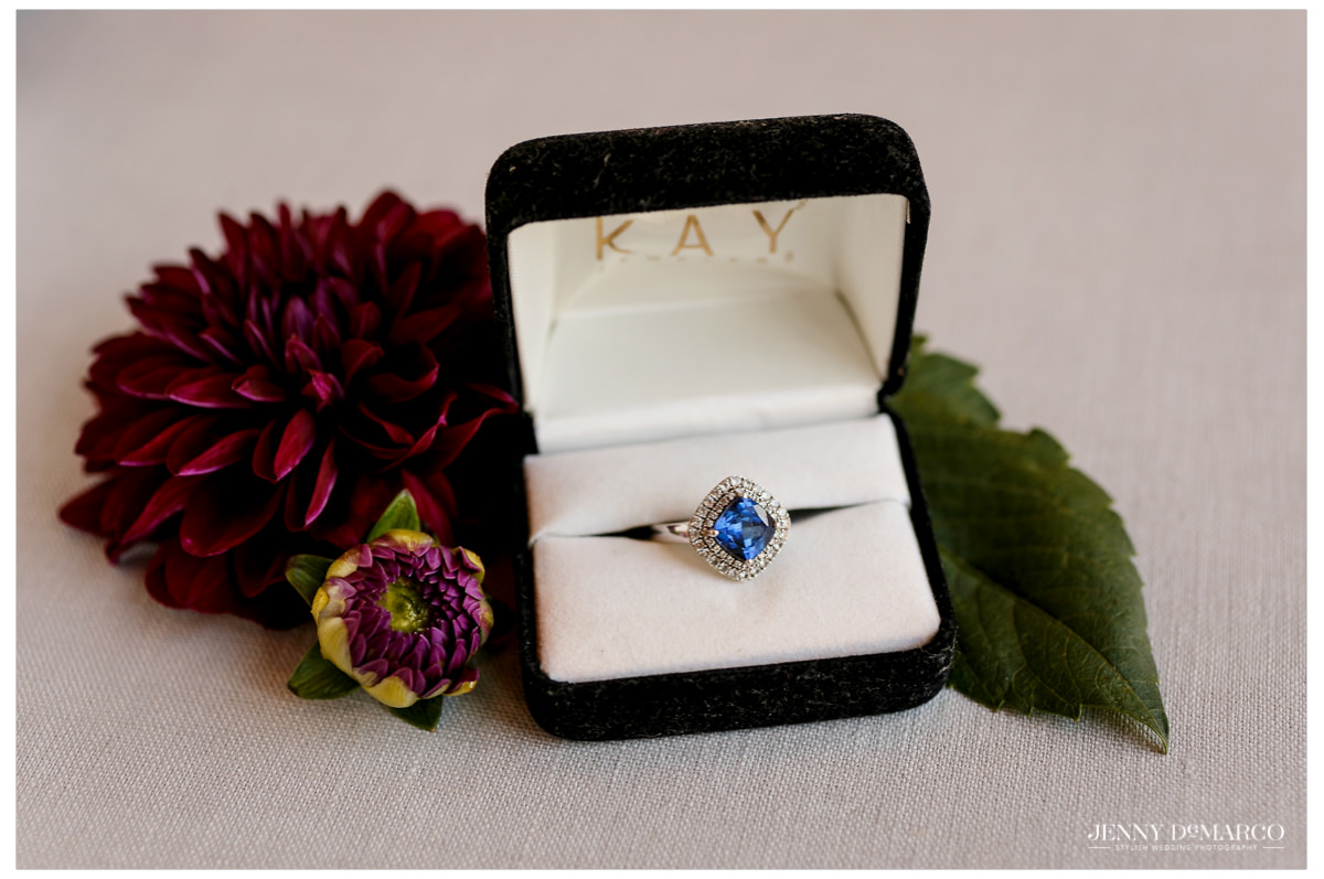 The bride wedding ring has a blue diamond in the center.