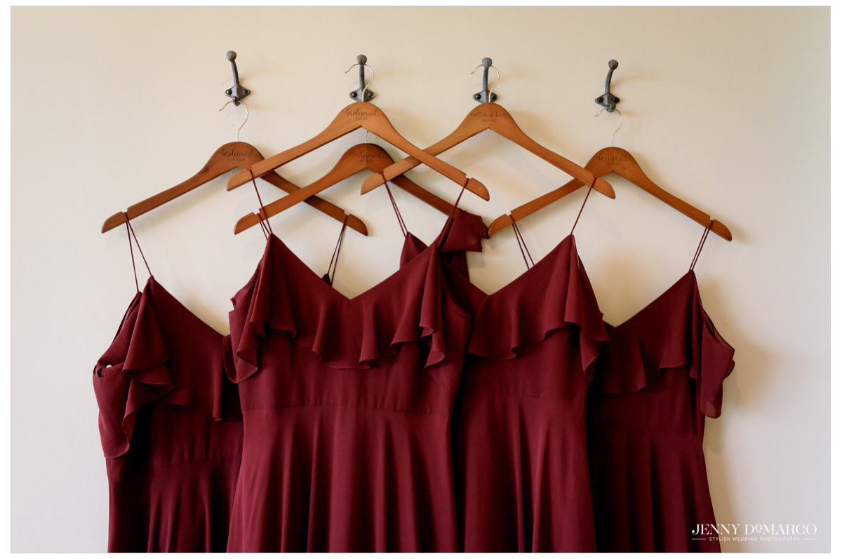 Bridesmaids red dresses line the wall.