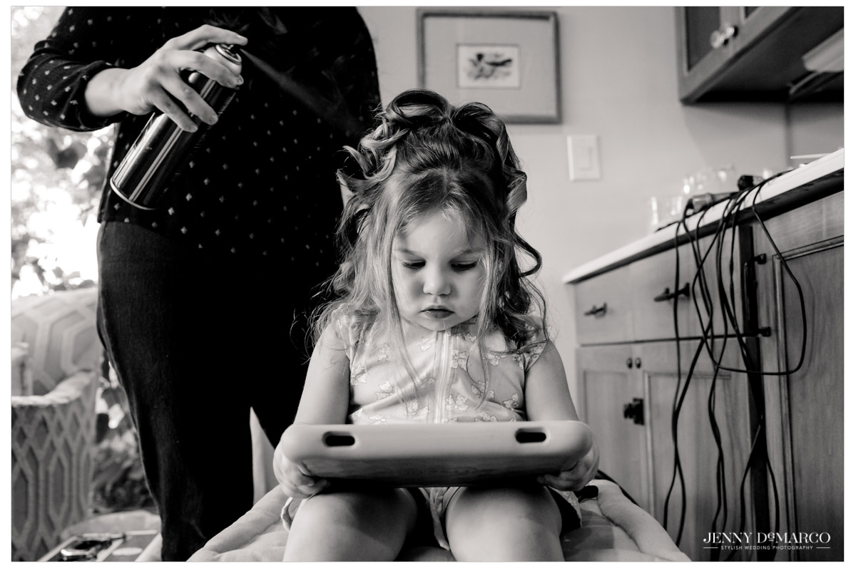 A little girl sits and watches tv while her hair gets done.