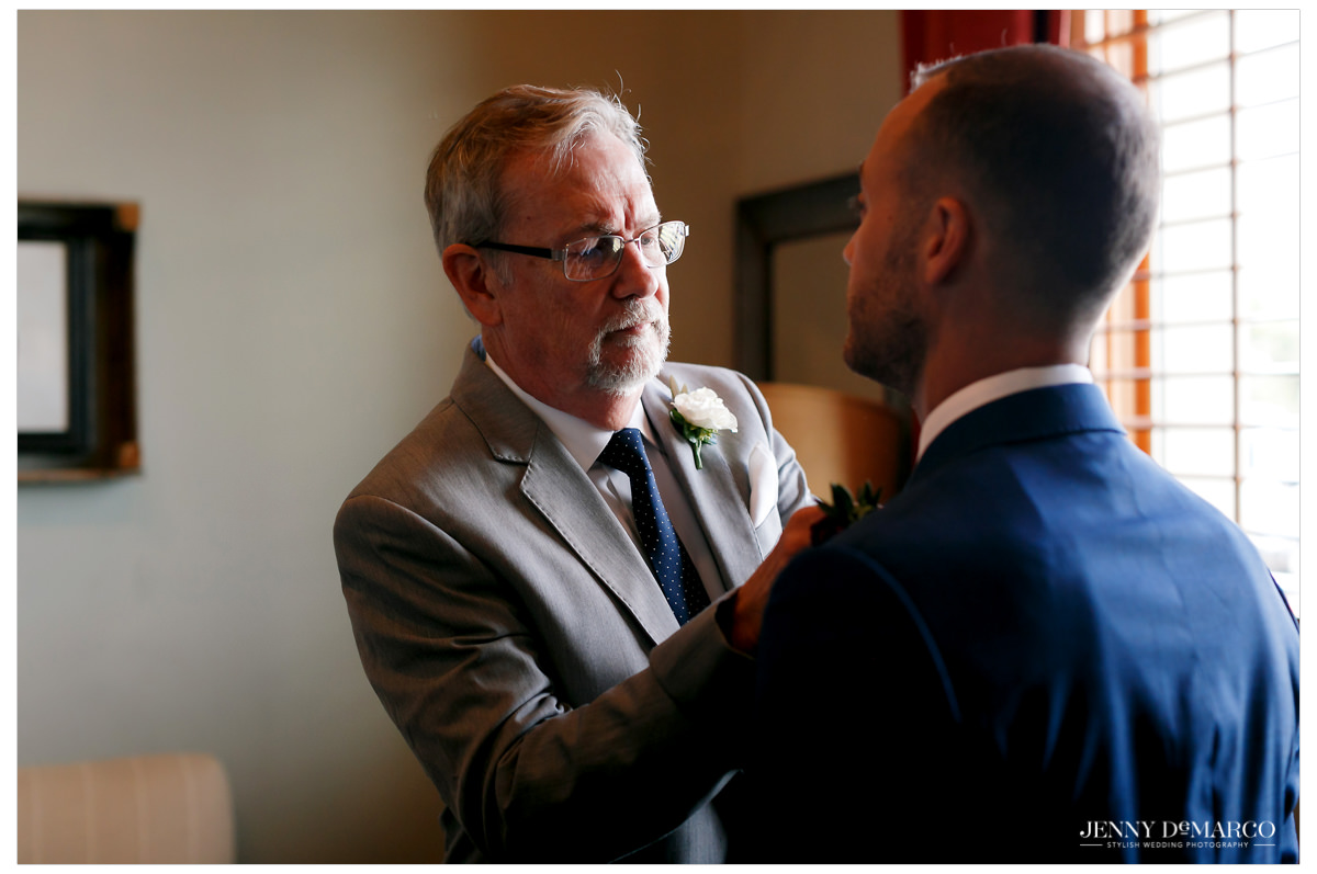 Father of the groom helps put on the groom's final touches.