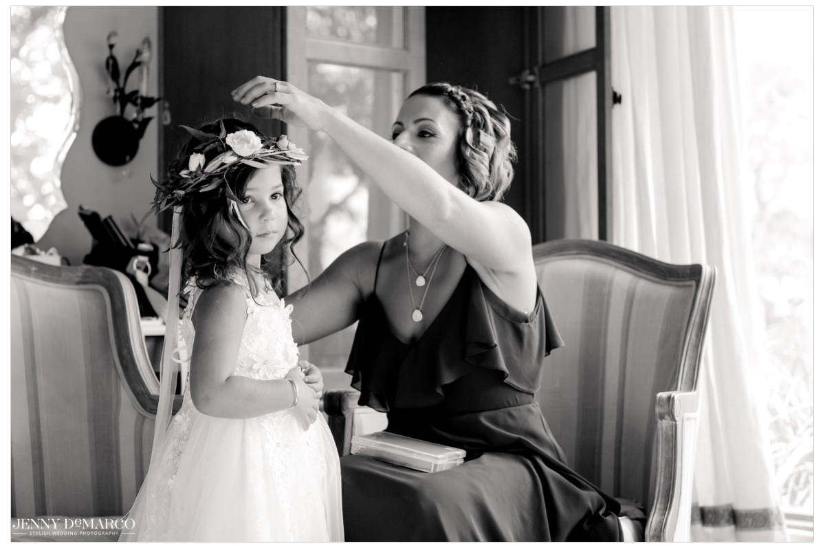 One bridesmaids helps put on the flower crown of the flower girl.
