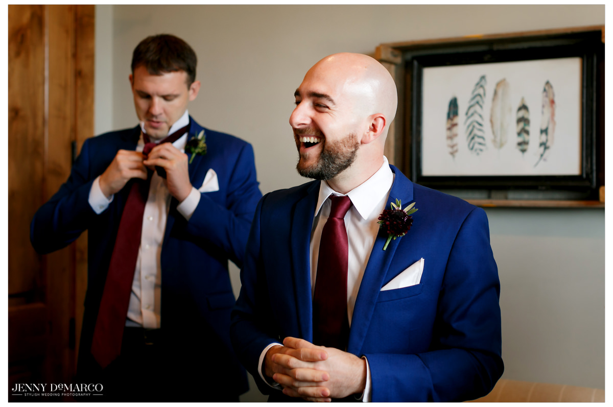 Groom laughs as he gets ready with his groomsmen.