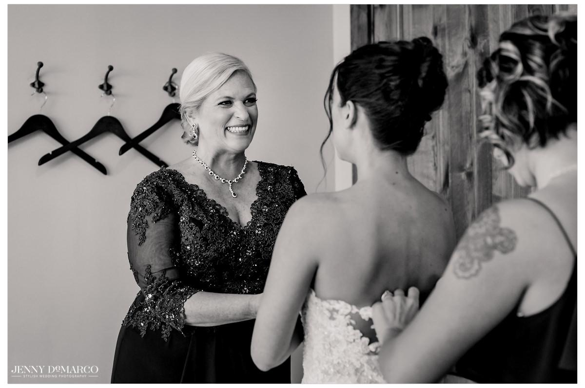 Mother of bride helps bride put on her wedding dress.