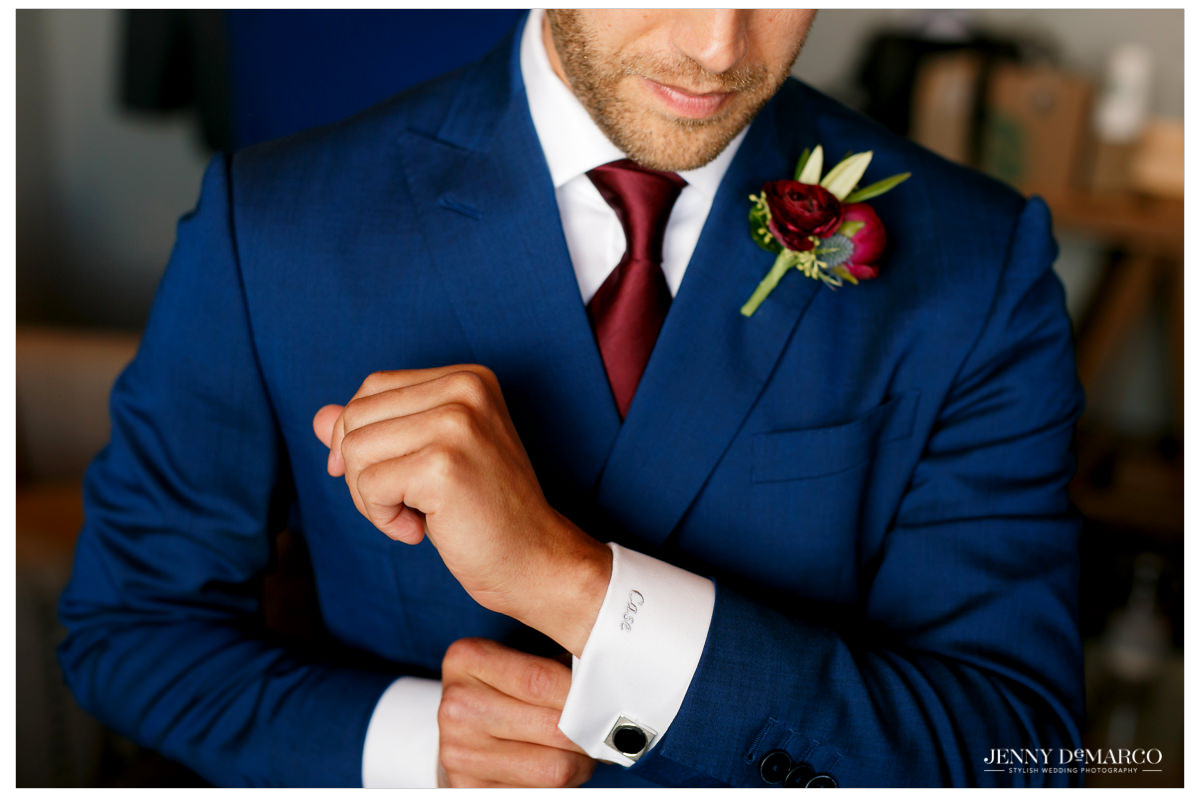 Groom poses for a shot as he fixes his cufflings.