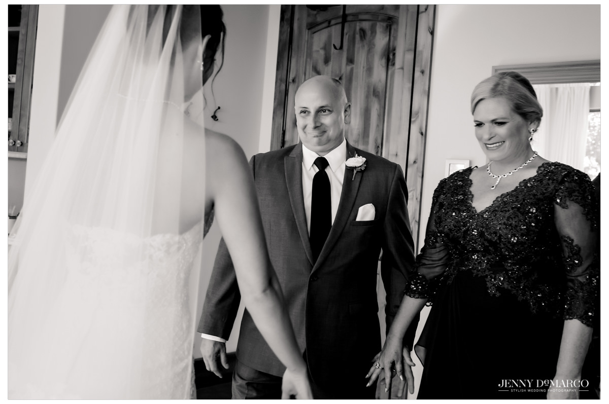 The parents of the bride look overly excited as the bride shows them her look.