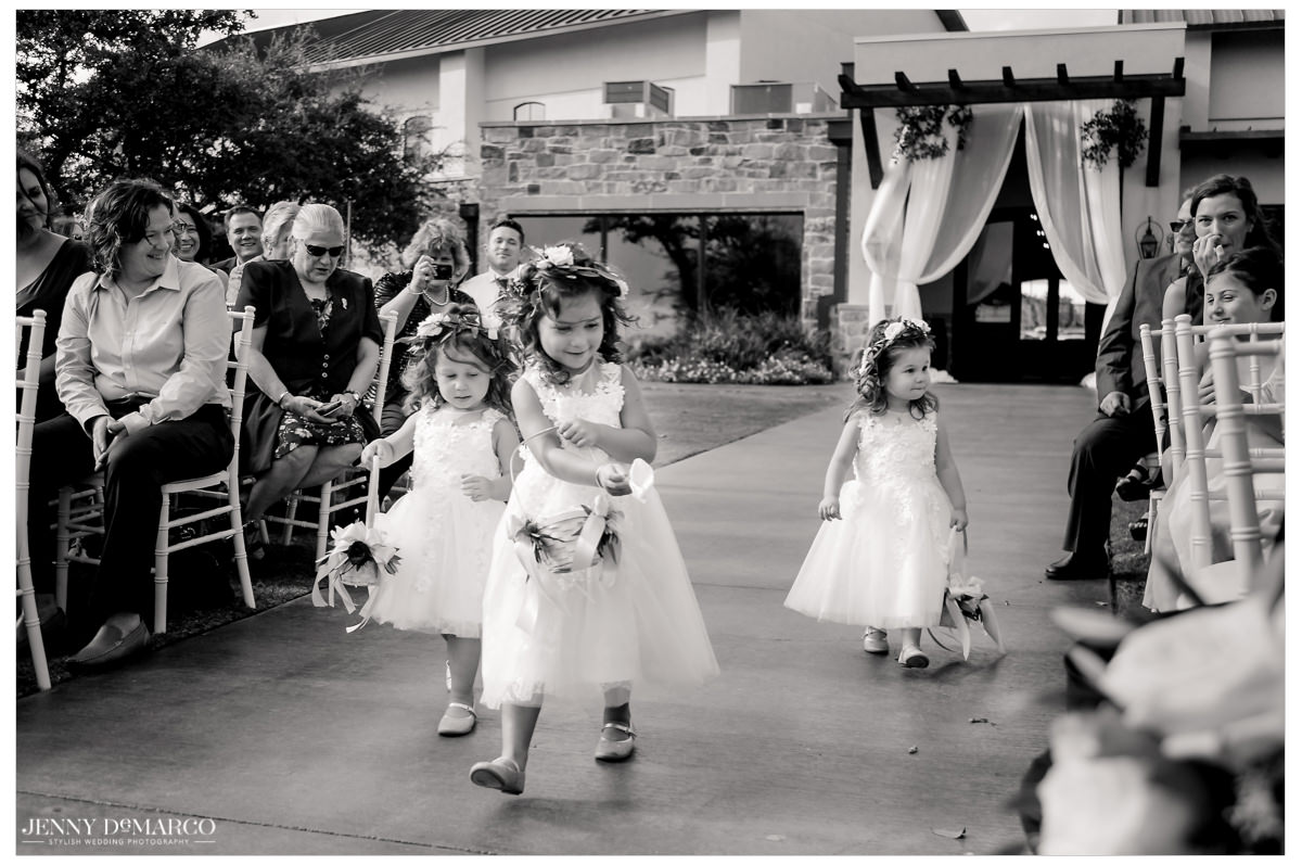 Three flower girls spread flowers all down the aisle.