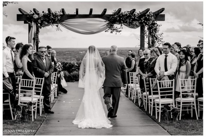 Father of the bride walks her daughter down the aisle.