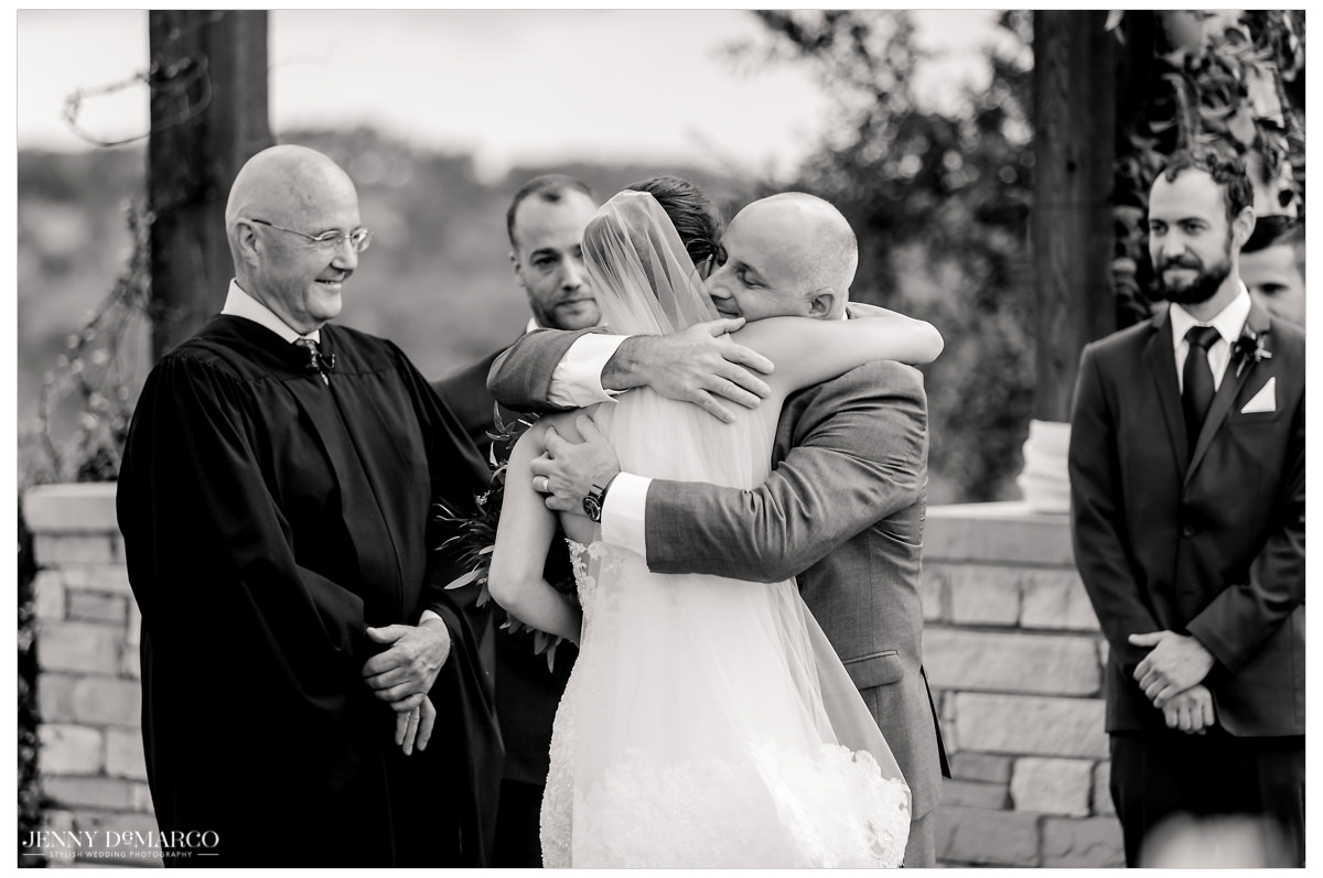 The bride hugs her father as he gives her away.