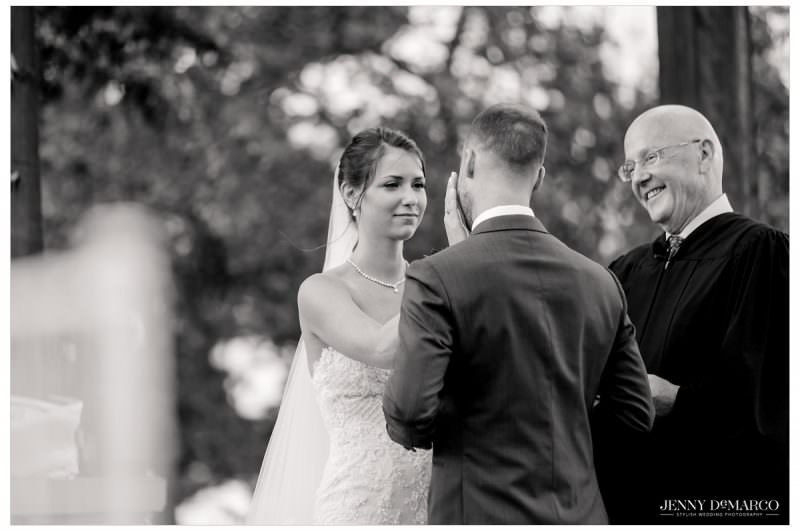 Bride wipes the tears off of the grooms face.