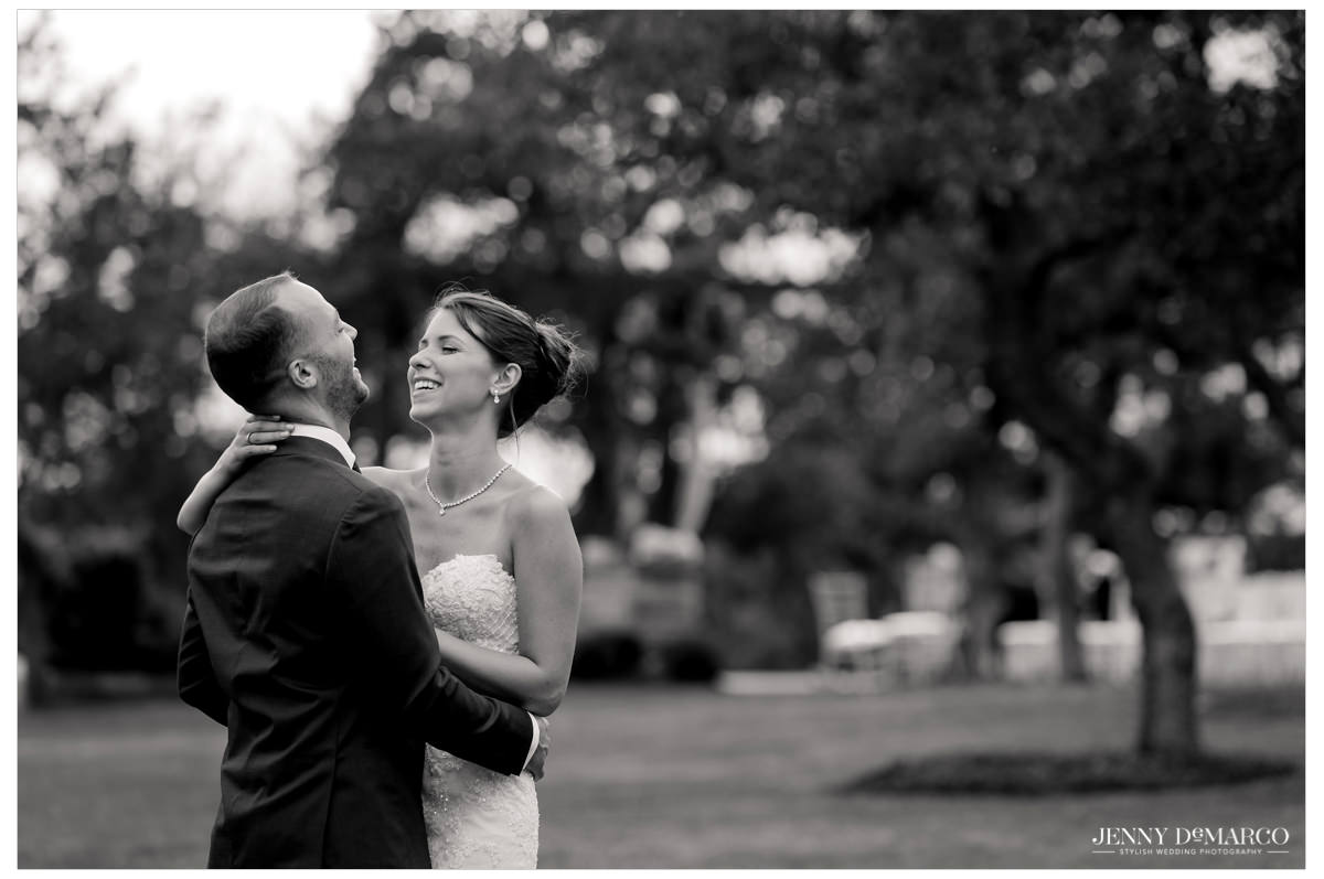 Bride and groom laugh as they embrace each other.