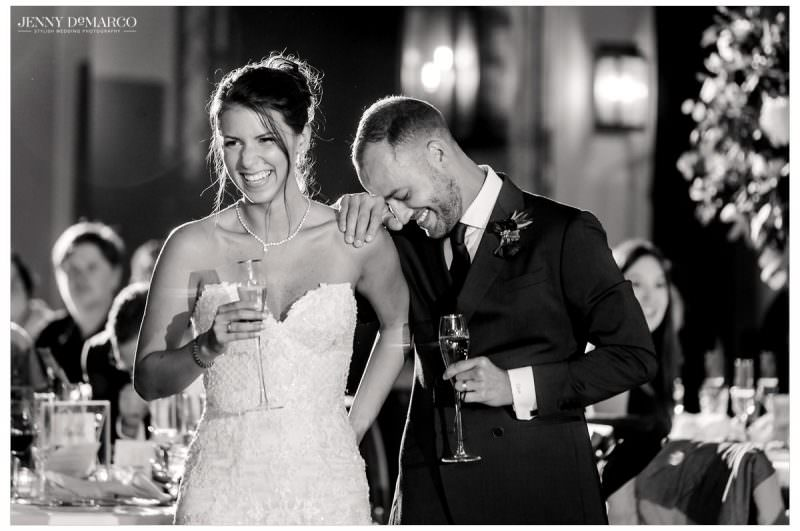 The couple laughs and leans on each other as they listen to speeches.