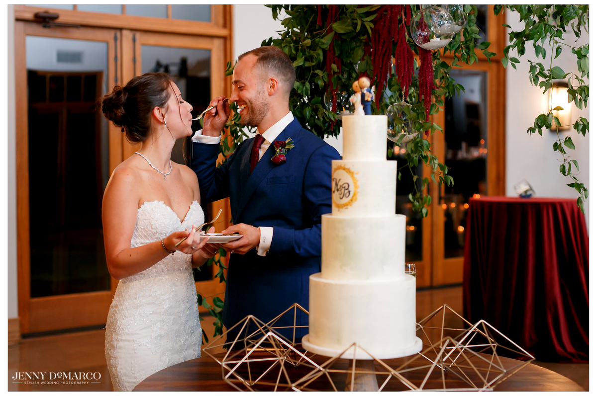 The couple gives a bite of their wedding cake to one another.