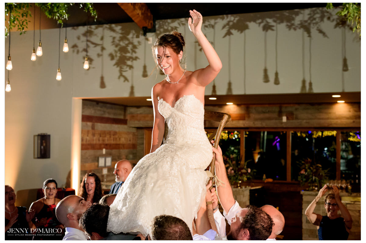 bride is lifted in a chair above her guests.