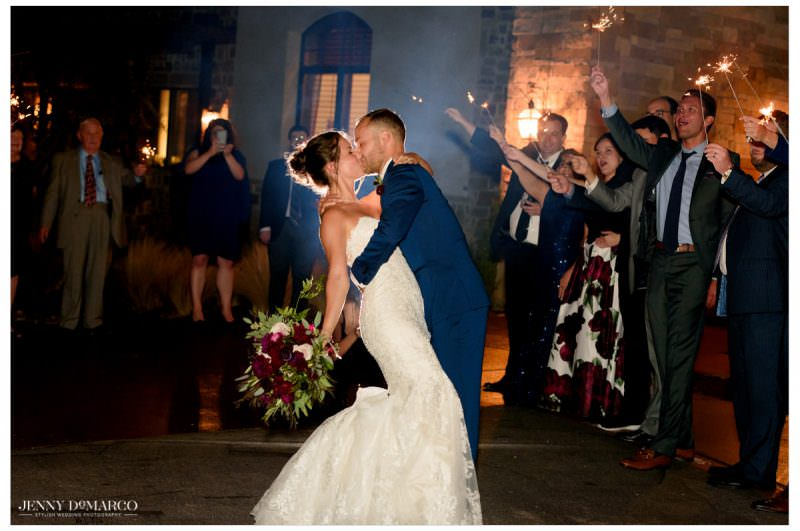 Bride and groom share the last kiss of the reception as guests surround them with sparklers.
