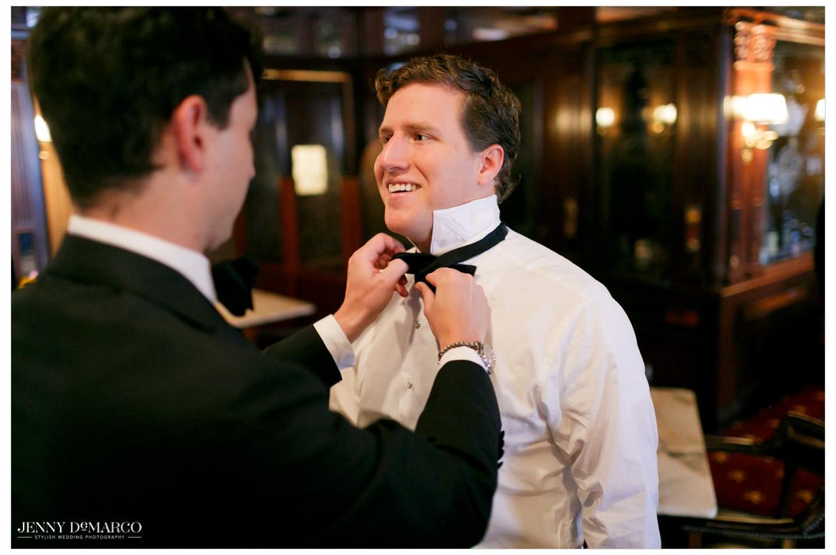 Groom gets help as he puts on his bowtie.