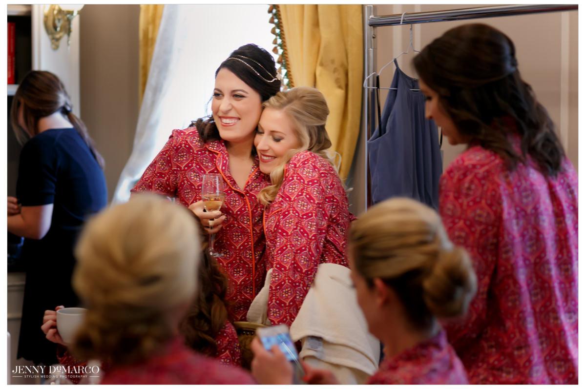 Bride hugs her bridesmaids.