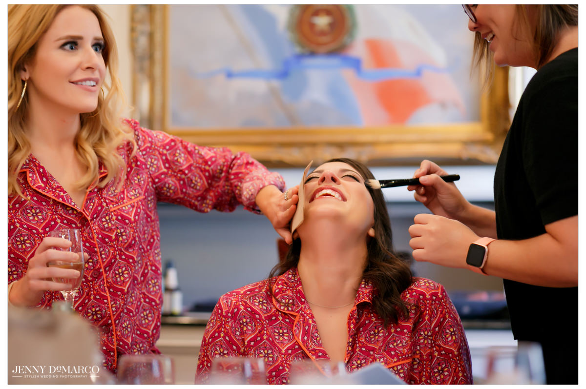 Bride throws her head backing laughing as they do her makeup.