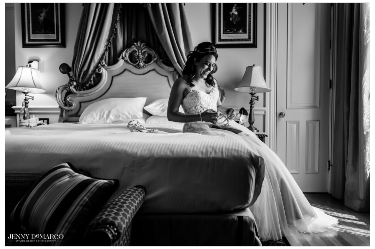 Bride sits on a bed as she puts on her heels.