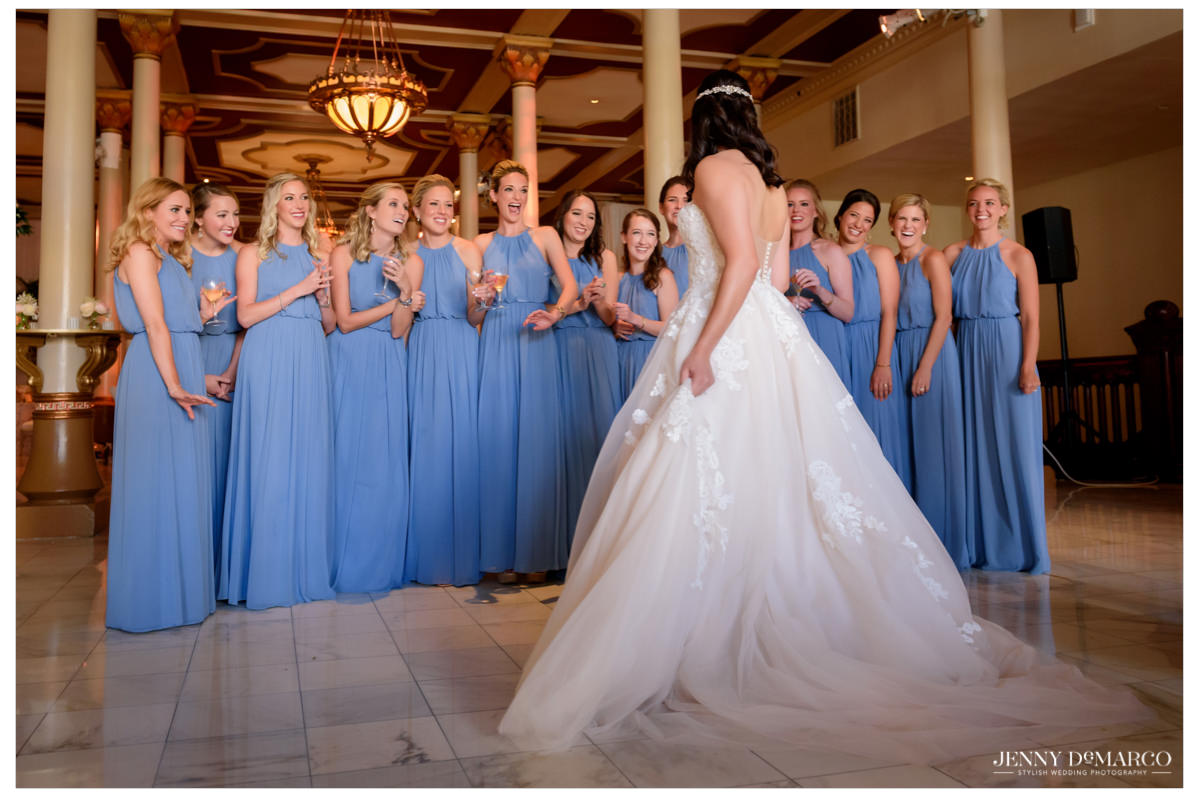 Bride shows off her look to her wedding party.