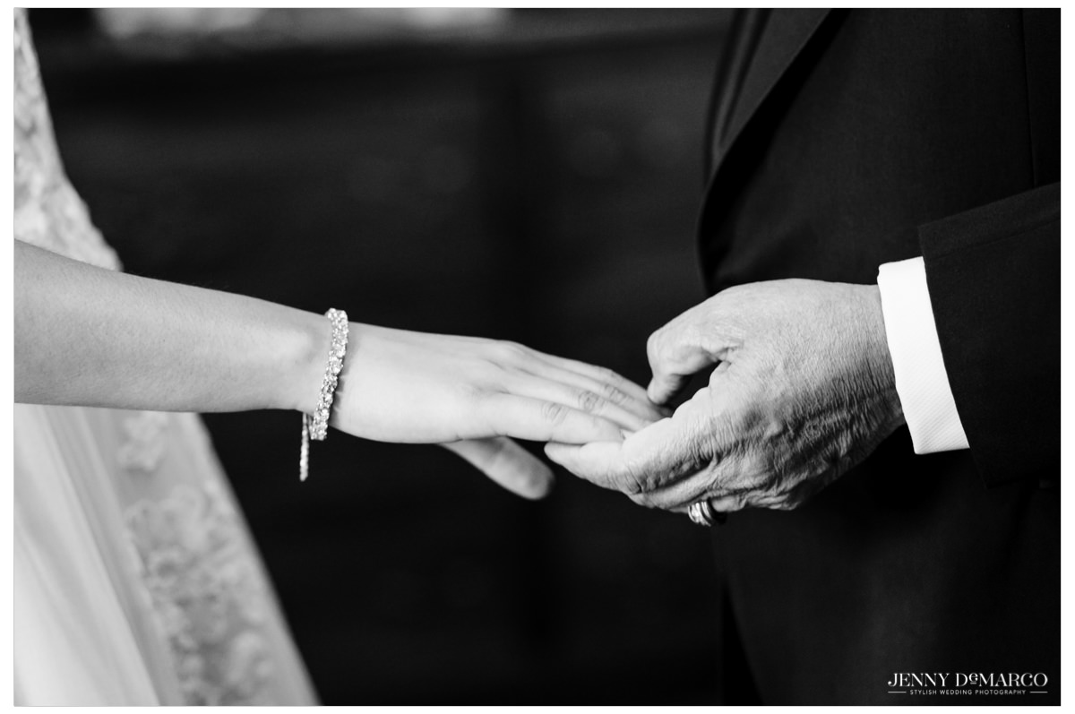 A detail shot of the father holding his daughter's hand.