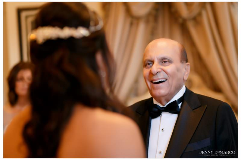 The father of the bride looks lovingly at his daughter.