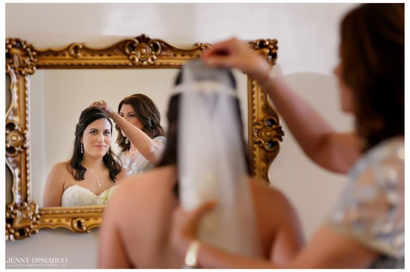 Bride looks in the mirror as the veil is put on her.