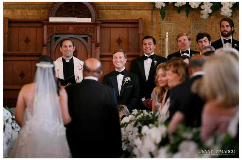 The groom has a big smile as the bride walks down the aisle.