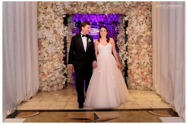 The couple enter the reception area under an arch of roses.
