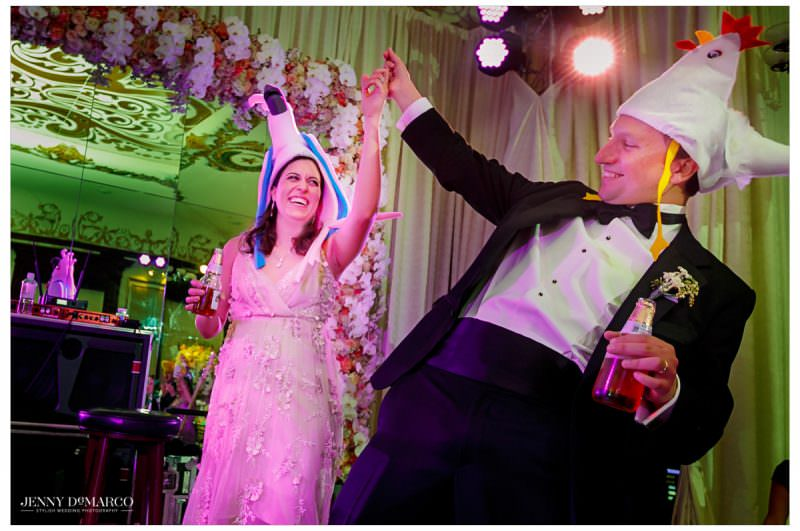 The couple puts on silly hats as they dance.