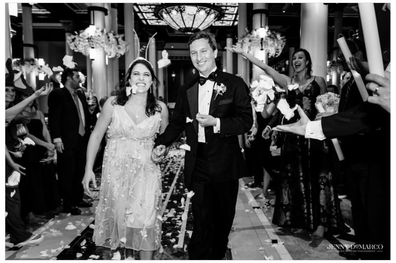 The couple ends the night as guests shower them with rose petals.