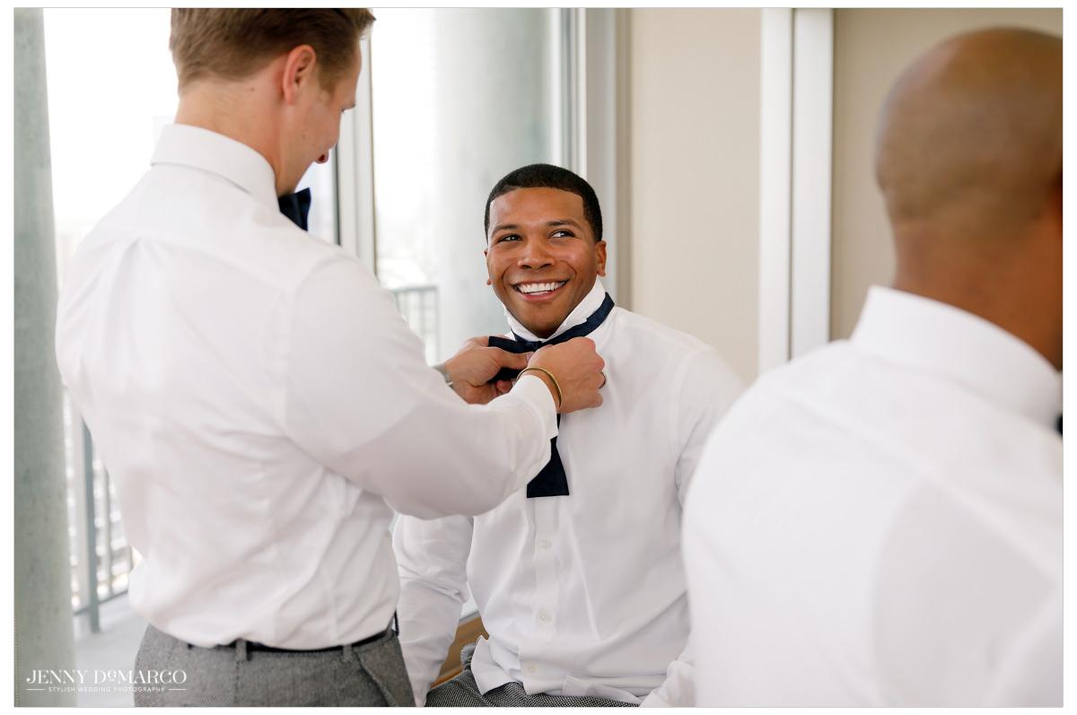 Groomsmen help the groom tie his bowtie.