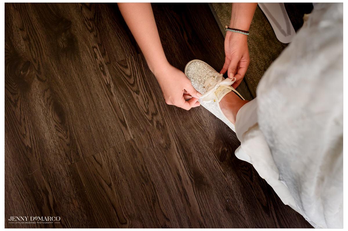 Bride ties her sparkly sneakers.
