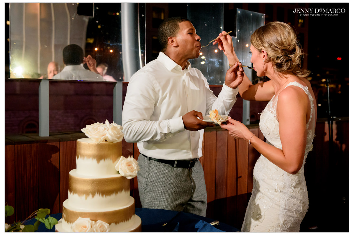 The couple feeds each other their wedding cake.