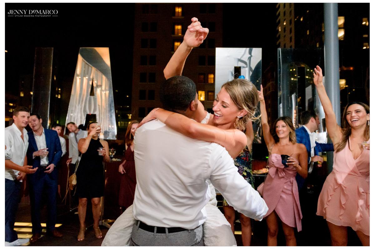 Bride jumps on groom as the dance floor gets rowdy.