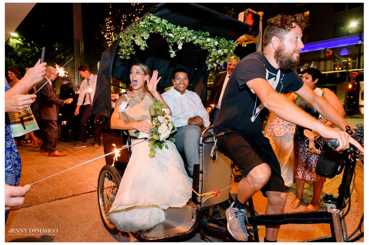 The couple rides away in a chariot.