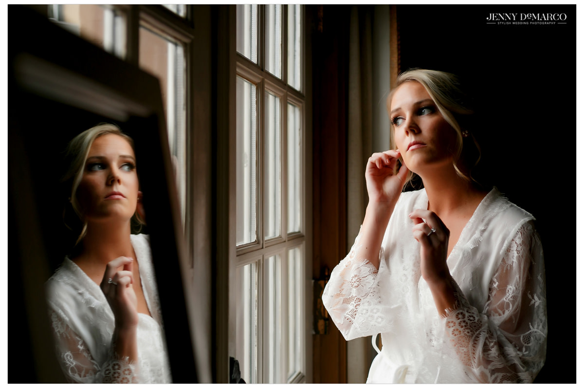 Bride puts on her earrings as she looks out the window.