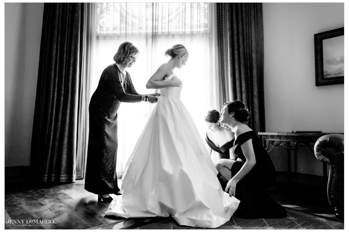 Bride gets help to make sure her satin wedding dress is fitting flawlessly.