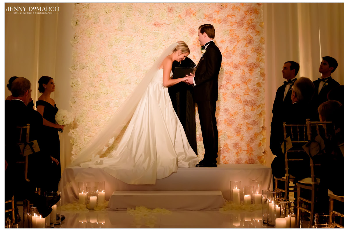 Bride laughs as she stands hand in hand with her fiancé at the altar.