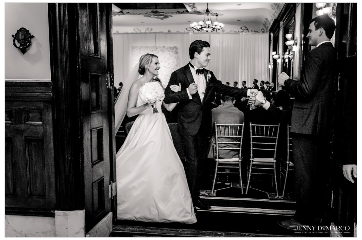 The couple exits the ceremony as guests cheer.