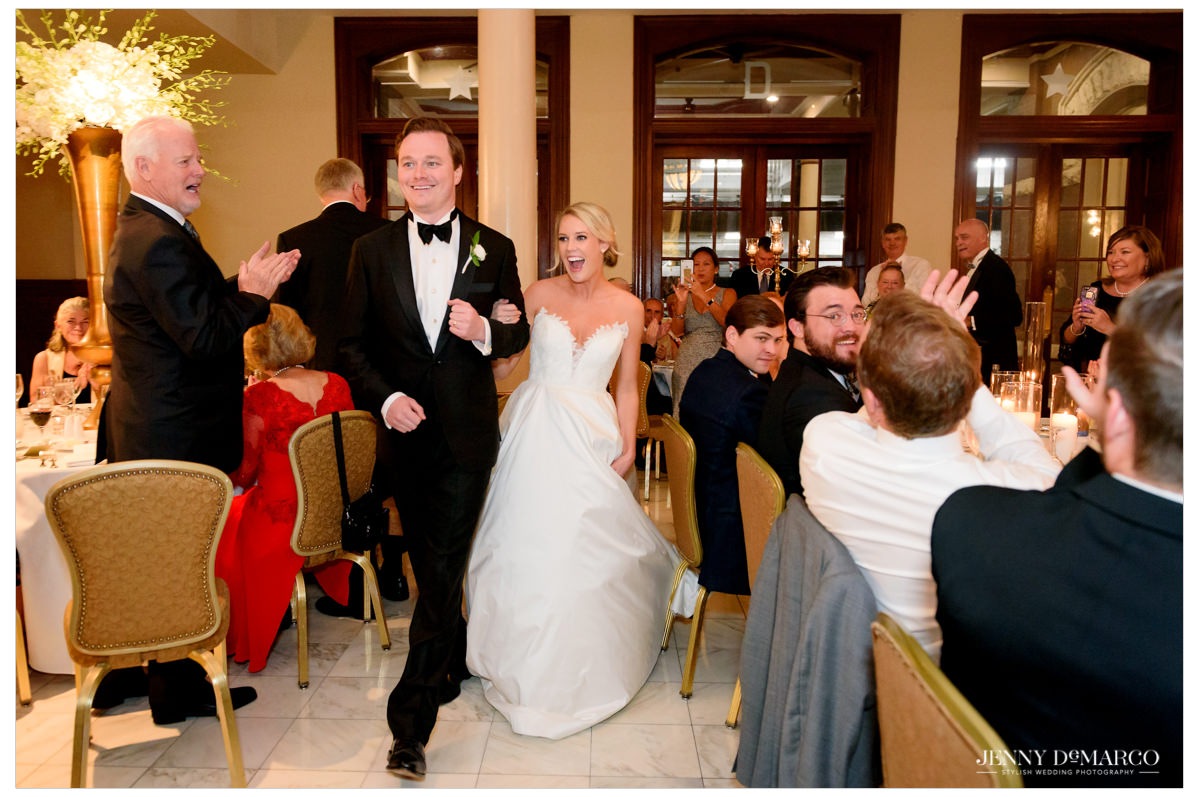Bride and groom walk arm in arm into the reception area.