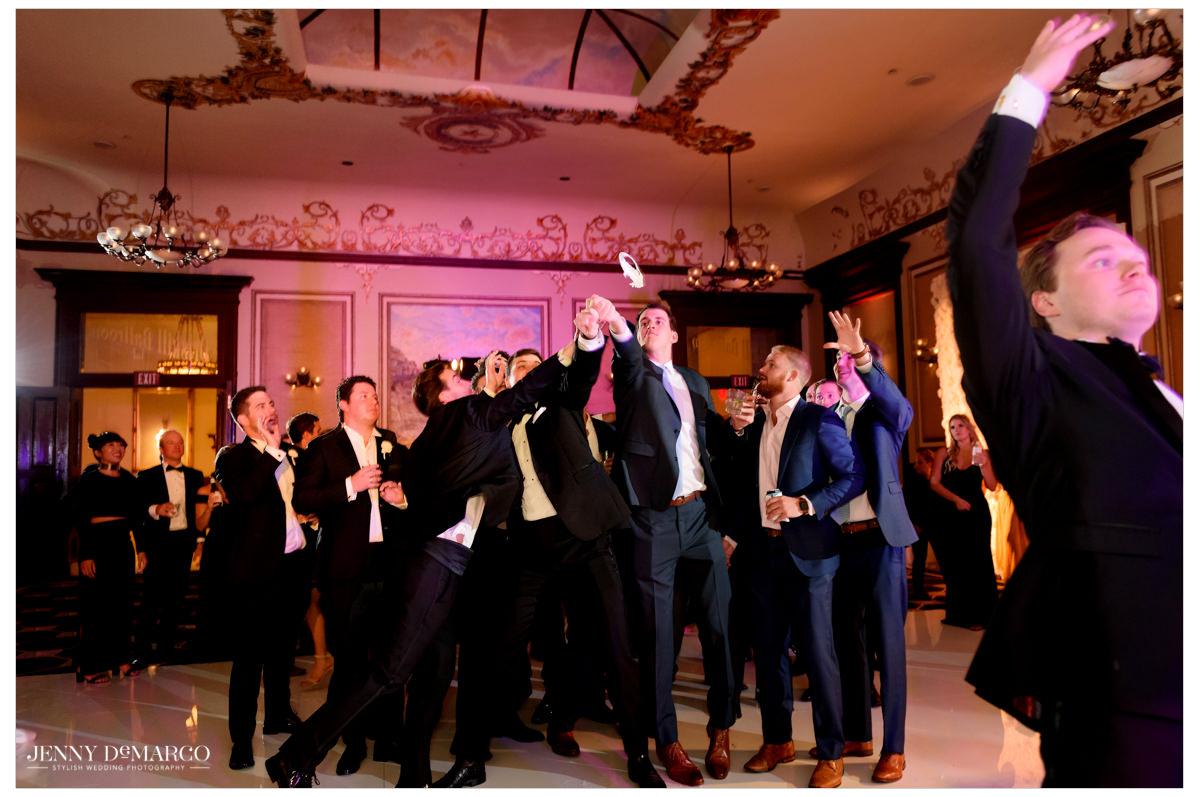 Groom throws the garter back towards the men.