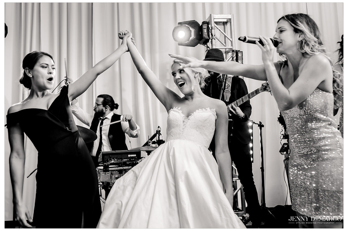Bride dances on stage with her fellow girlfriends.