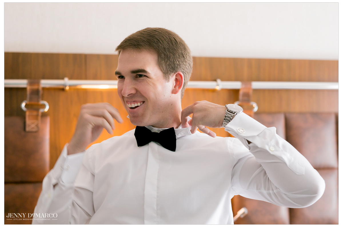 Groom puts on his bow tie.
