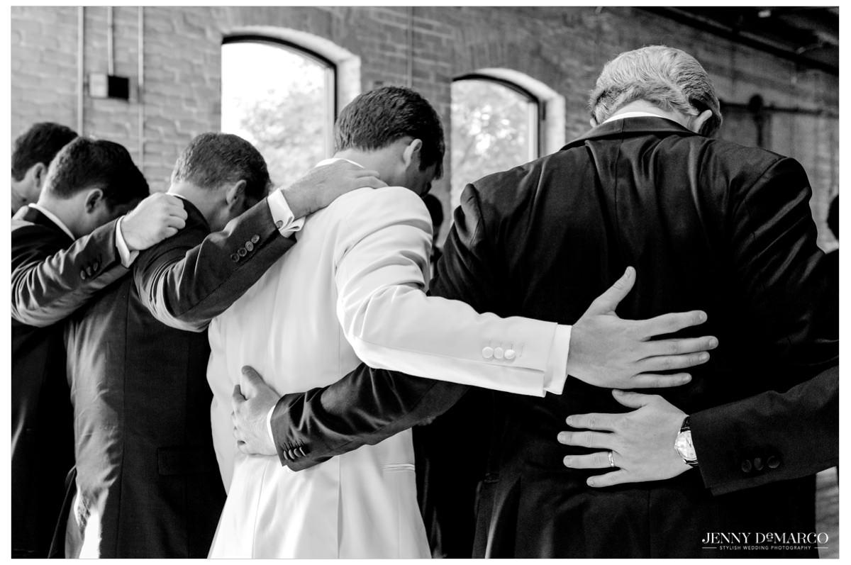 The groomsmen pray over the groom.