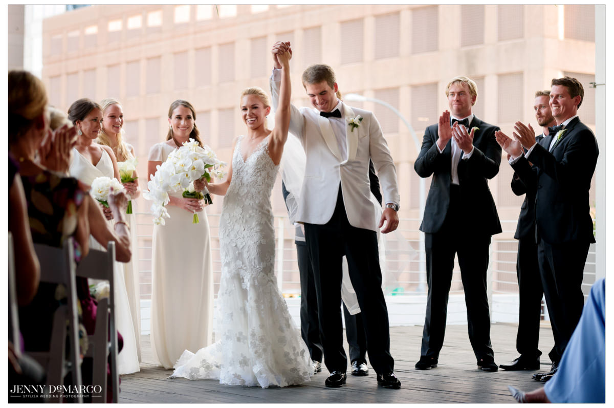 Bride and groom raises their hands in celebration.