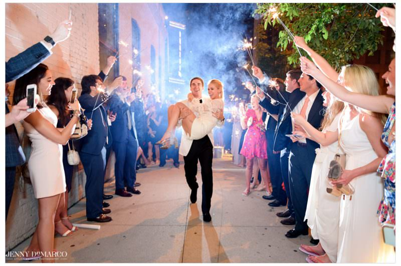 The groom carries out his wife as guests surround them with sparklers.