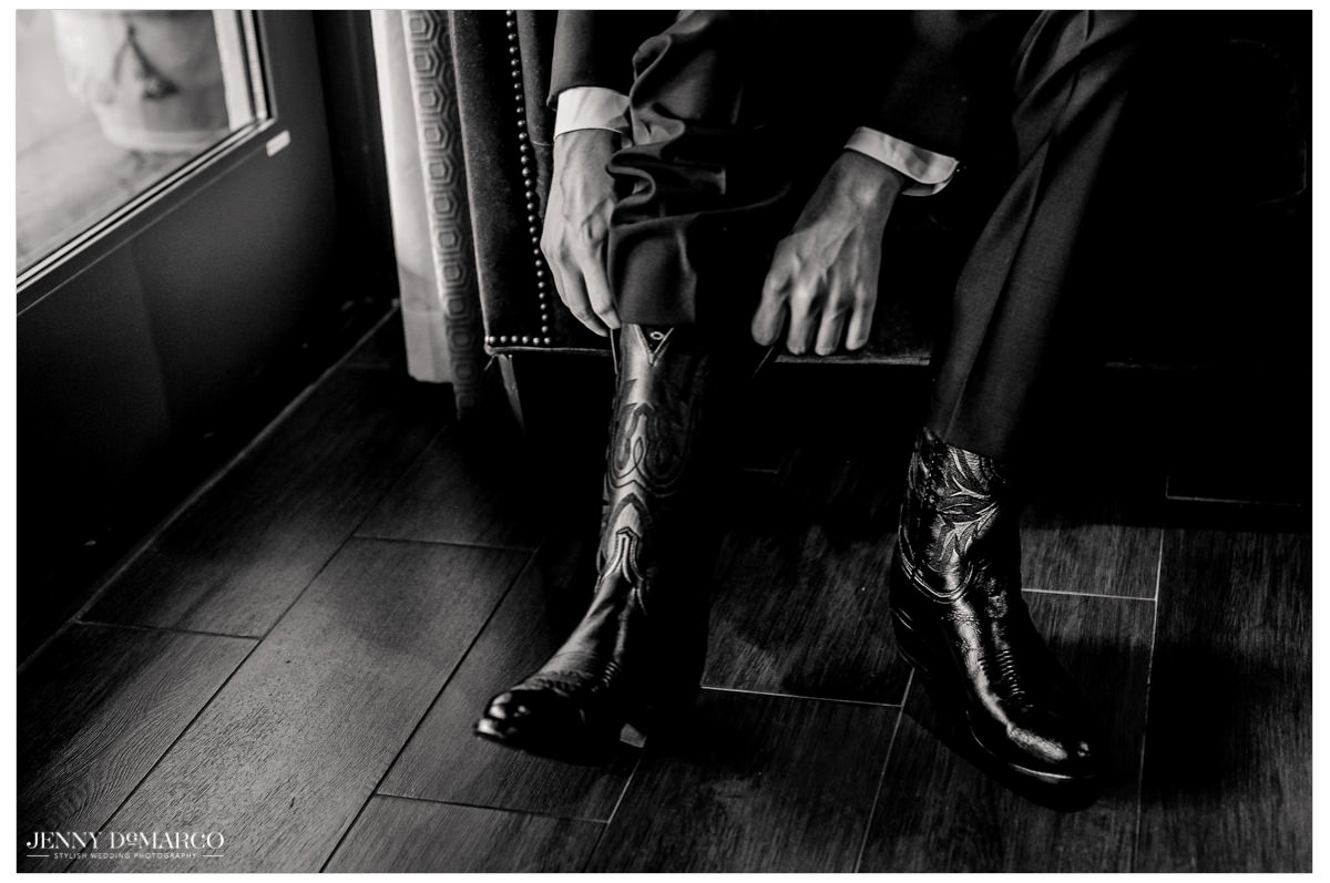 Groom outs on his cowboy boots for the final touches.