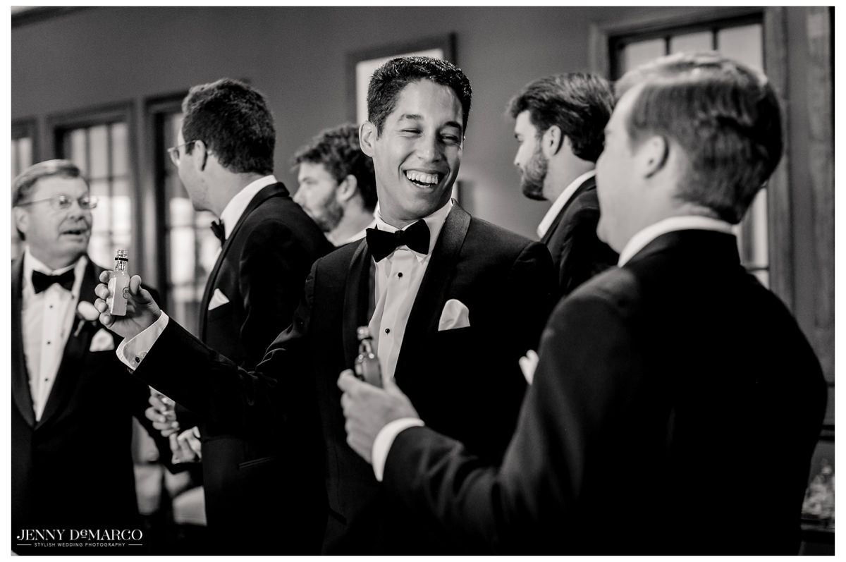 Groomsmen gather around to take a shot of alcohol together.